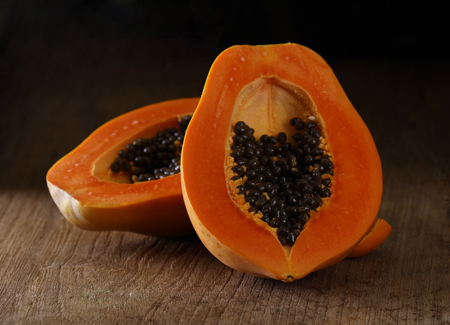 Papaya is half cooked on wooden floor.