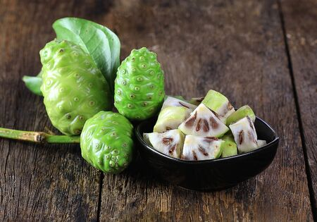 Noni fruit sliced on wooden boards