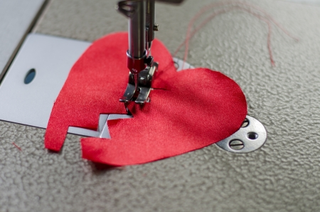 close up of a stitched red cloth broken heart  Stock Photo
