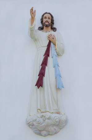 Stone sacred heart Jesus statue with shallow depth of field.