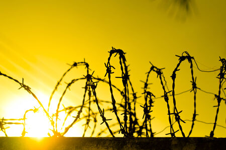 symbol fence: Barbed wire fence and Light of Hope. Stock Photo