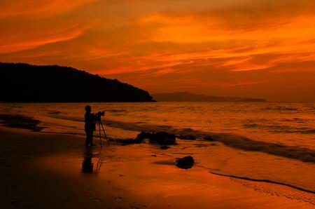 Photogrpher running at sunset on the beach. Stock Photo