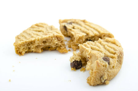 Chocolate chip cookie with a bite taken out and crumbs, isolated over white background. Stock Photo