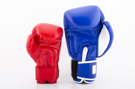 Close up of red and blue boxing gloves bumping isolated on white background Stock Photo