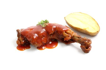 Cooked chicken wings in a sauce and potato isolated in white background photo