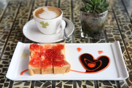 slice of bread with strawberry jam and coffee photo