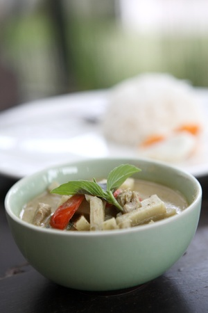 Thai food green curry witn rice in wood background photo