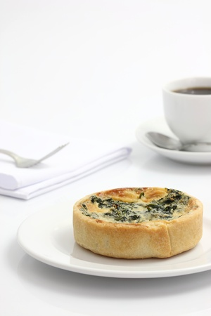 spinach quiche pie with coffee isolated on white background photo