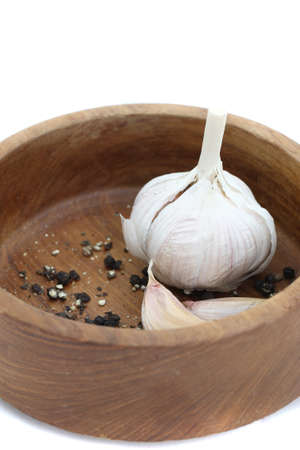 garlic and pepper on wood bowl isolated in white background photo