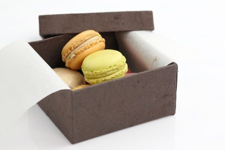 Colorful Macaron in paper box isolated on white background photo