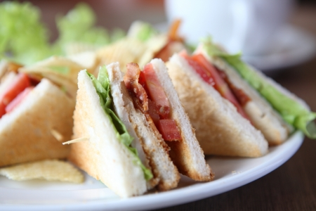 ham sandwich: Club sandwich with coffee on wood background