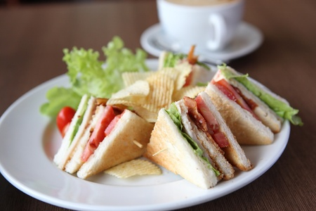chicken sandwich: Club sandwich with coffee on wood background