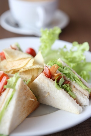toasted: Club sandwich with coffee on wood background