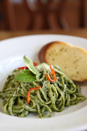 spaghetti with pesto sauce on wood background photo