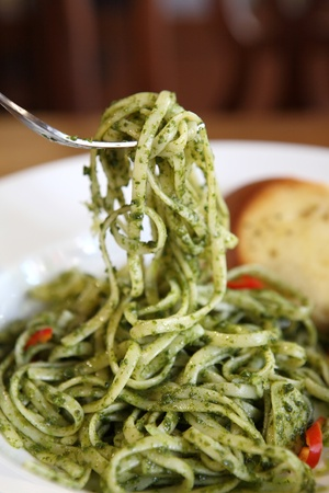 spaghetti with pesto sauce on wood background photo
