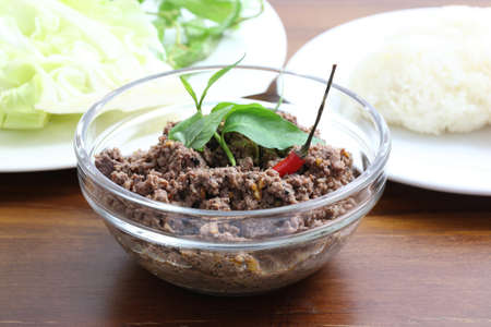 Thai food minced meat with vegetable and chilli on wood background photo