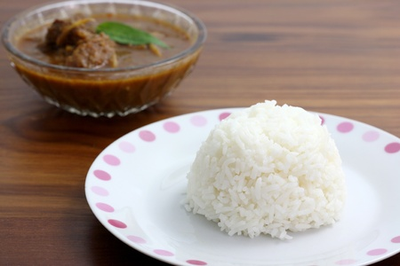 Thai food pork curry with rice in wood background photo
