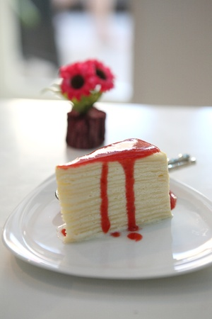 Crape cake pour with strawberry sauce on plate  photo
