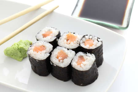 Salmon Maki sushi with chopsticks and soy sauce in white background photo