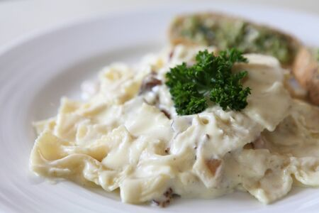 Farfalle pasta with white sauce and bacon photo