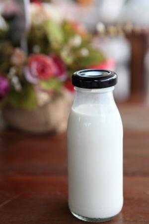 milk in bottle on wood background photo