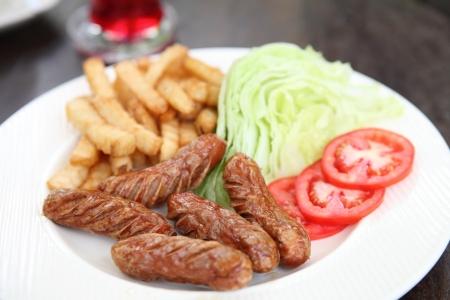 Sausage with potato on wood background photo