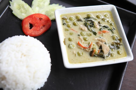 Thai food chicken green curry with rice in wood background photo
