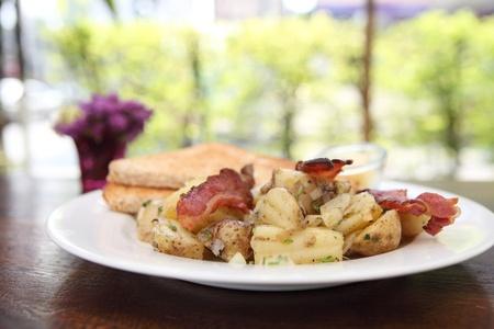 papas doradas: El desayuno de tocino, tostadas y croquetas de patata. Foto de archivo
