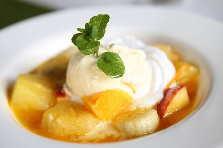 mix fruit flambe banana orange and apple with ice cream photo