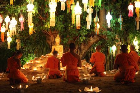 Thai monks meditate around buddha statue among many lanterns