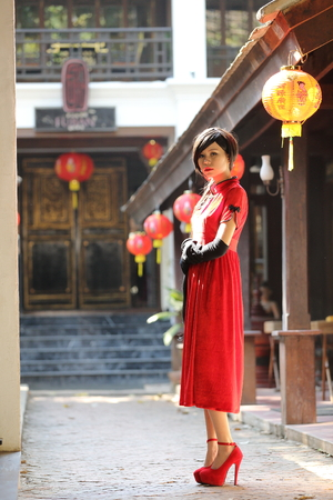 qipao: happy Chinese new year. beautiful young Asian woman dress traditional cheongsam