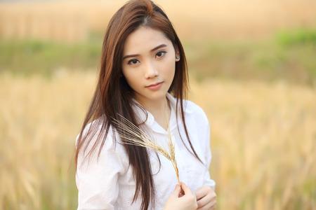 Asian girl on wheat field Stock Photo