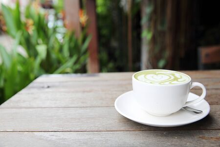 frothy: green tea latte on wood background