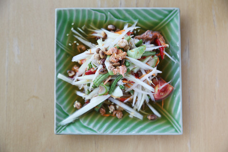 green papaya salad: Green papaya salad on wood background