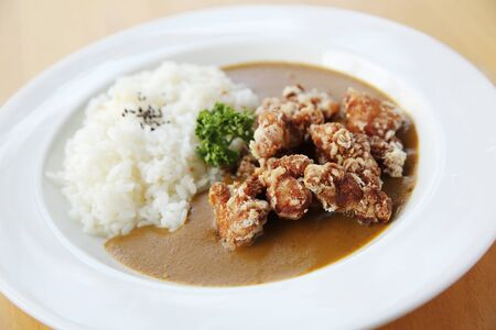 japanese cookery: Curry rice with fried chicken on wood background
