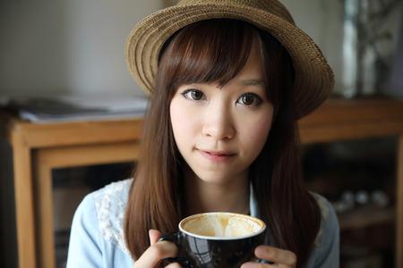 アジアの女の子の屋内はコーヒーを飲む