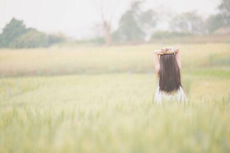 niñas chinas: muchacha asiática se relaja en campo de trigo Foto de archivo