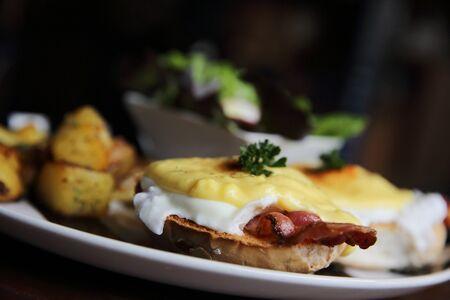benedict: egg benedict with bacon and potato on wood background Stock Photo