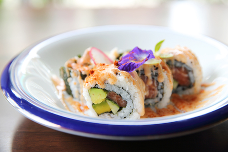 cebollines: atún y salmón uramaki aguacate con salsa picante en primer plano Foto de archivo