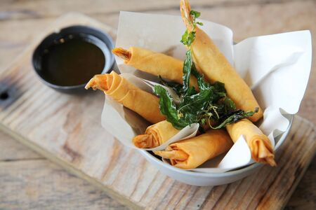 appetiser: Spring rolls with shrimp with sweet chili sauce. Asian food on wood background