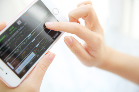trading online on smartphone with business woman hand Standard-Bild