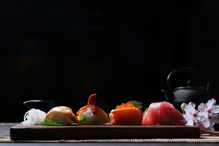 Sushi Set sashimi and sushi rolls with tea on wood background