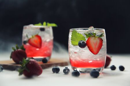 Strawberry juice cocktail with ice and mint on black background and smoke