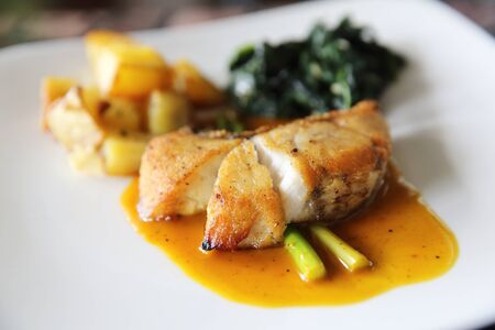 Sea bass fillet steak with potatoes and spinach in lemon sauce