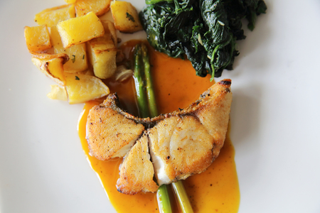 chilean: Sea bass fillet steak with potatoes and spinach in lemon sauce