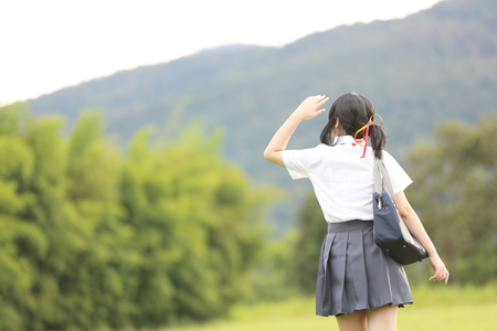 Japanese school in countryside with grass mountain and tree