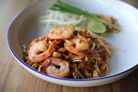 Pad thai with shrimp . Thai food on wood background