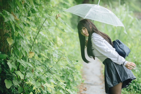 Portrait of Asian school girl walking with umbrella at  nature walkway on raining Banque d'images