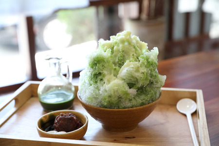 Delicious Japanese sweet shaved ice green tea on wooden table in japanese cafe Stock Photo