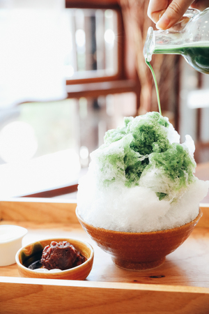 Delicious Japanese sweet shaved ice green tea on wooden table in japanese cafe 免版税图像